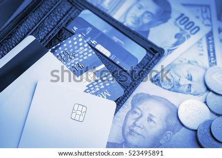 Money in a virtual form or a digital money such as credit cards on a pile of banknotes and coins with a black leather wallet. An idea of a modern life style nowadays that most things are intangible.