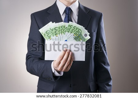 Money in an envelope in the hands of men on gray background - stock photo