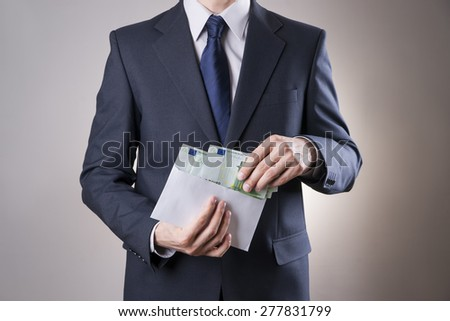 Money in an envelope in the hands of men. To count euro on gray background - stock photo