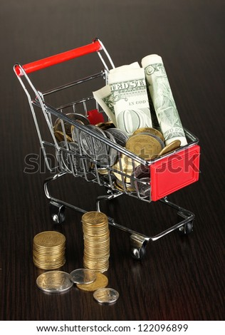 Money in cart isolated on black