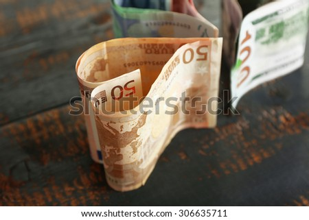 Money in form of hearts on rustic wooden table, closeup - stock photo