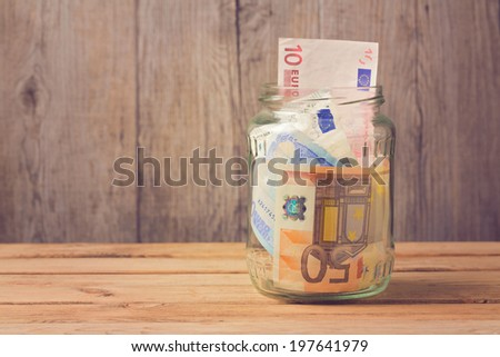 Money in glass jar on wooden table - stock photo