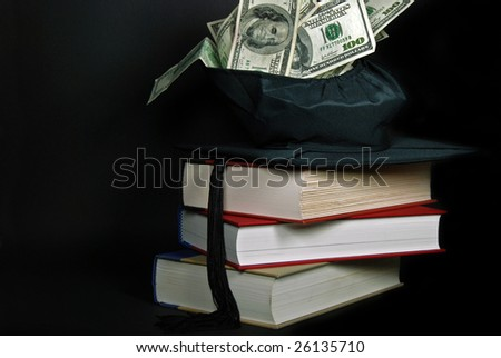 money in graduation cap on books - stock photo