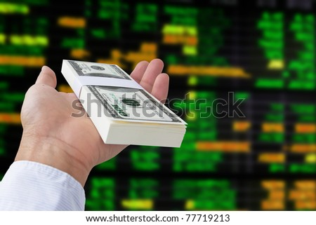 money in hand on stock exchange board background - stock photo