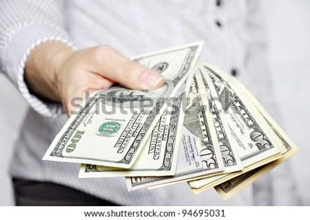 Money in human hands closeup, shallow DOF - stock photo