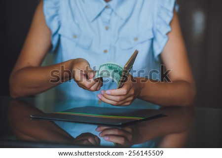 Money in human hands, women counting a lot of 100 dollars, with business folders , on a black background - stock photo