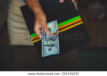 Money in human hands, women giving 100 dollars, with business folders , on a black background - stock photo