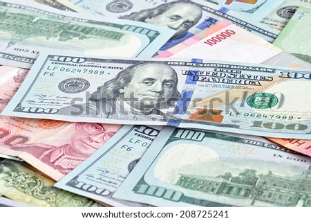 Money in multi currencies with 100 USD bill on top - stock photo