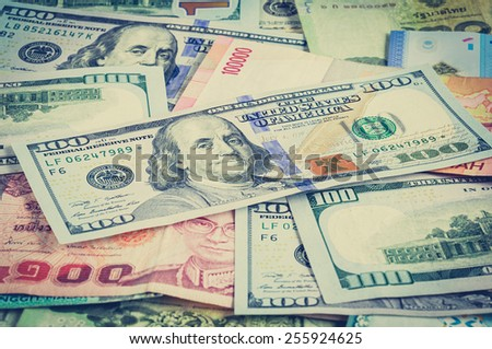 Money in multi currencies with 100 USD bill on top - vintage (retro) style color effect - stock photo