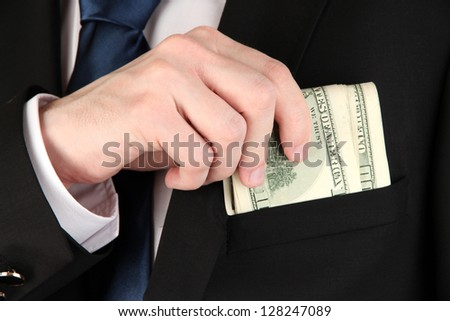 Money in pocket of businessman close-up - stock photo