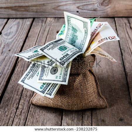 money in sackcloth and coins scattered on a wooden background - stock photo