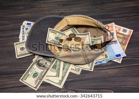 Money in the old cap. Financial concept background - stock photo
