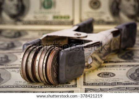 Money is tight concept Coins in clamps on one hundred dollar bills  - stock photo