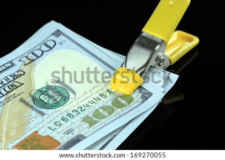 Money is tight concept US one hundred dollar bills squeezed tight in a tool clamp - stock photo