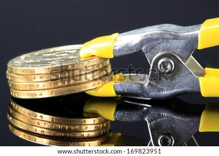 Money is tight - Credit Crisis Stack of Gold Coins in Clamp - stock photo