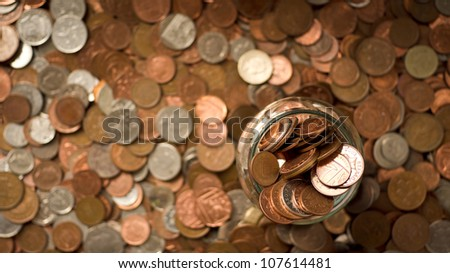 money jar on a pile of coins - stock photo