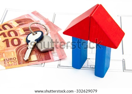 Money, key chain and house made with blocks on the plan