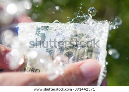 Money laundering, five euro banknote under water drops in a rain. - stock photo