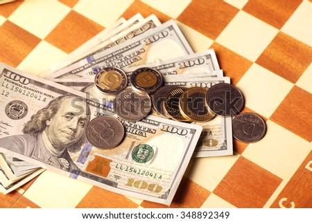 Money on a chessboard, furnyt euro dollar - stock photo