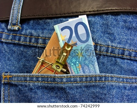 Money on a mouse trap in back pocket of denim jeans - pickpocket crime concept - stock photo