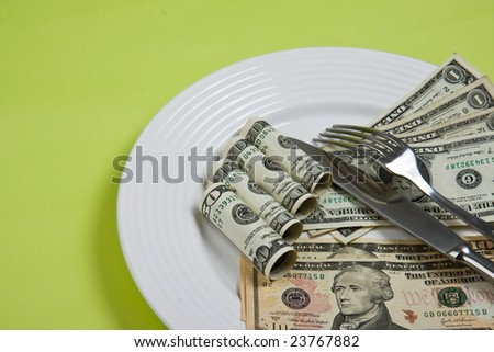 money on plate with fork and knife