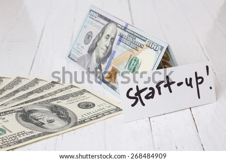 Money on the table. Idea, concept of start up. Hundred dollars. Banknotes on the table. A lot of dollars. The theme of the business, entrepreneurship, profit, start-up capital. - stock photo