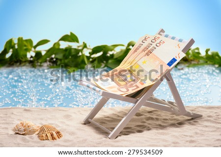 Money on vacation, pack of fifty Euro bills sitting at the beach on a sun lounger in front of a blue lagoon - stock photo