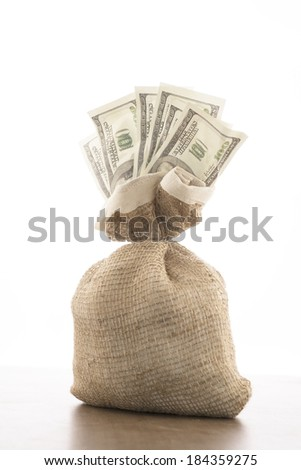 Money one hundred dollar bill in the burlap sack bag  isolated on brown table background