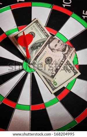 Money pierced by arrow on dartboard close up - stock photo