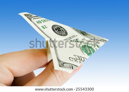 money plane on the fingers over blue sky - stock photo