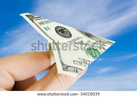 money plane on the fingers over sky with clouds - stock photo