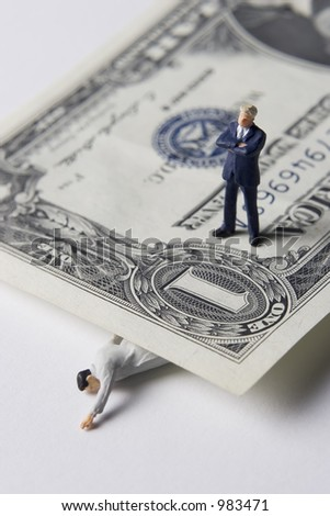 Money problems, business figure standing on dollar - stock photo