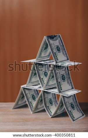 Money pyramid on wooden table, close up - stock photo