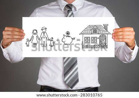 Money saving concept.Business man holding a drawing of a family,saving money to buy a house. - stock photo