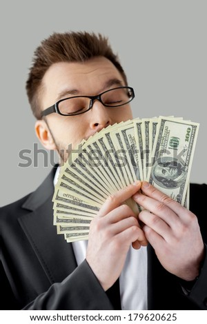 Money smelling. Confident young man in formalwear and glasses holding paper currency and smelling it while standing against grey background