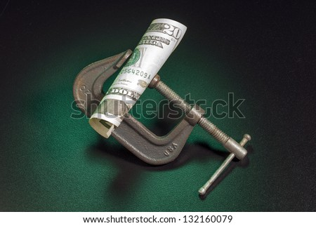 Money squeeze as a metaphor for inflation and increase in taxes - stock photo