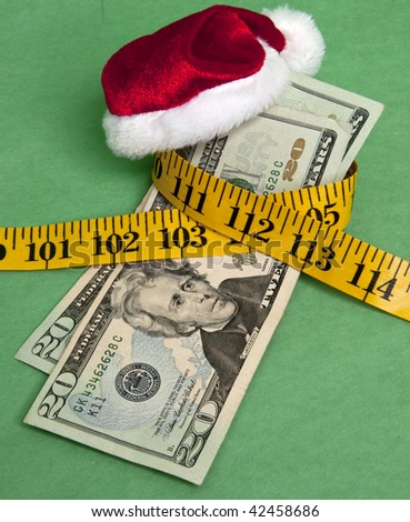 Money squeezed by a measuring tape representing a tight holiday budget. - stock photo
