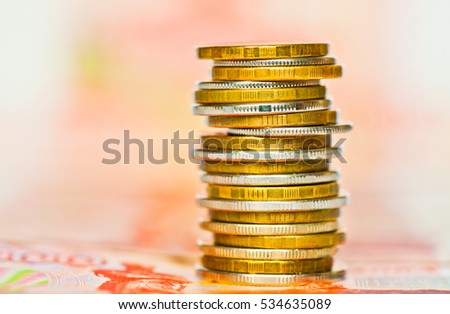 Money. Stack of rubles coins against 5000 rubles banknotes background
