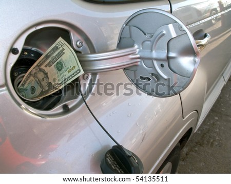 Money sticking out of automobile fuel tank opening signifying and illustrating the high cost of gas. - stock photo