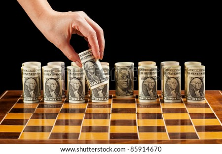Money strategies concept - dollar bills on chess board manipulated by woman hand - stock photo