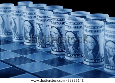 Money strategy concept with dollars as pieces on chess board - in cold blue shades - stock photo