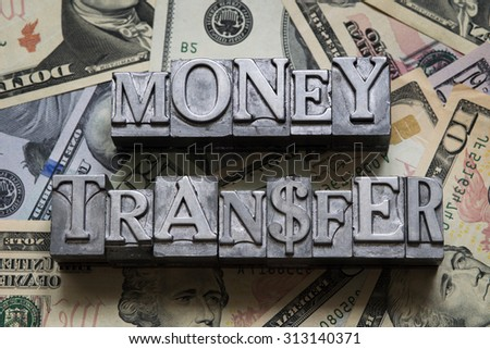 money transfer concept made from metallic letterpress type on heap of US dollars - stock photo