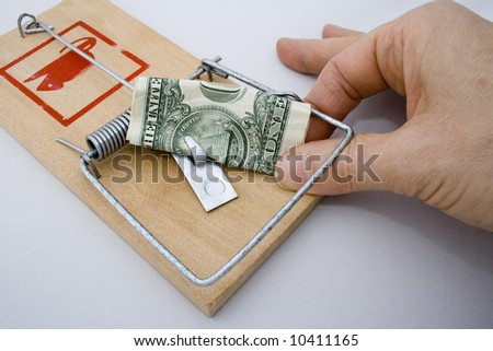 Money Trap - Gold Coin being taken from a rat trap - stock photo