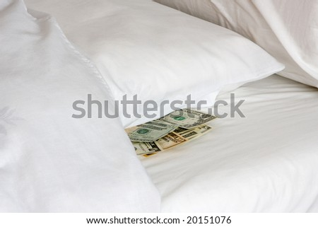 Money tucked away under a pillow during financial crisis - stock photo