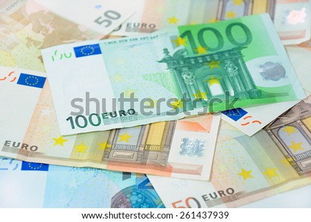 Money, various kinds of Euro currency bills with 100 bill on top - soft focus - stock photo