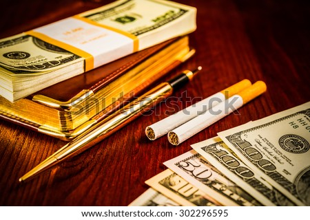 Money with a leather diary and cigarettes with golden pen on a mahogany table. Image vignetting and hard tones