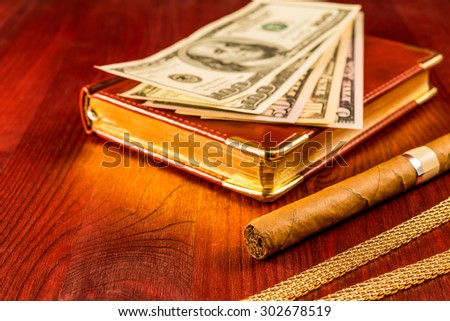 Money with a leather diary and cuban cigar with jewellery on a mahogany table. Focus on the cuban cigar