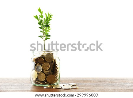 Money with growing sprout in glass jar on table isolated on white - stock photo