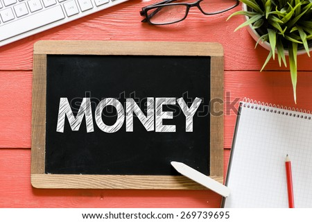 Money word Handwritten on blackboard. Money word Handwritten with chalk on blackboard, keyboard,notebook,glasses and green plant on wooden background - stock photo