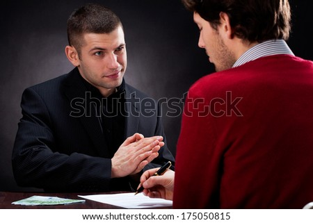 Moneylender convincing client to sign usury contract - stock photo